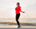 young attractive woman doing sport exercises in morning sunrise on sea beach in sports wear, healthy lifestyle, listening to music on earphones, wearing pink windbreaker jacket, jumping in jump rope